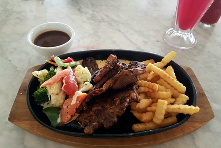 sumptuous: Tasty and delicious grilled lamb chop with vegetables and fries for side dishes served on a hotplate Stock Photo
