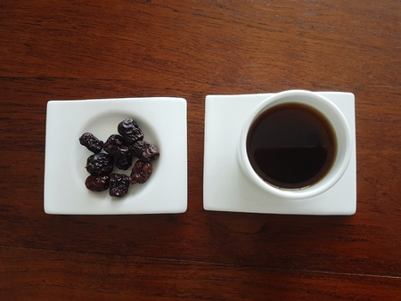 nourishing: High angle view of healthy Chinese Red dates tea drink and whole fruit served on white plate and cup for promotion of health and complexion, set on wooden table.