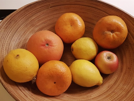 Close-up display of a group of mix healthy fruits- oranges, grapefruit,  lemons and apple in big wooden bowl