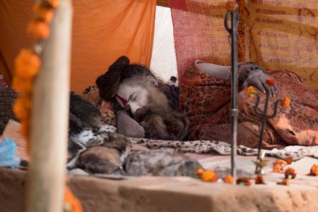 south asian ethnicity: KATHMANDU, NEPAL - FEBRUARY 17, 2015: An unidentified Napalese sadhu (holy man) takes a nap during the Maha Shivaratri Festival at Pashupatinath Temple, on February 17, 2015 in Kathmandu, Nepal. Editorial