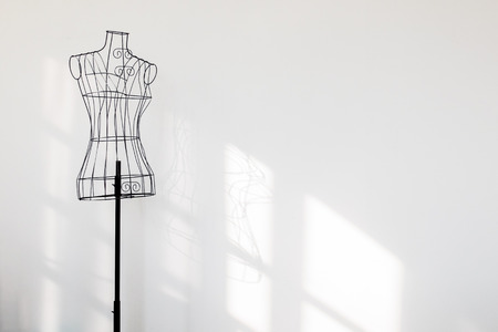 made: Vintage mannequin stand at white wall.