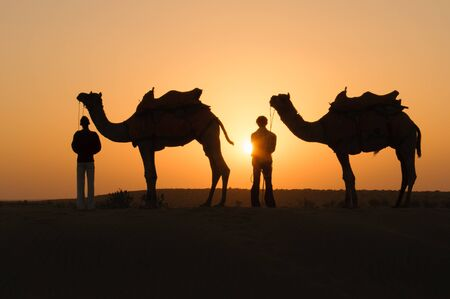 thar: JAISALMER, INDIA - NOVEMBER 15,2008: Silhouette of unidentified local people and camels at sunset on November 15,2008 in Thar desert near Jaisalmer, Rajasthan, India.