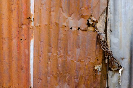 locked the door: Old and rusty damaged galvanized iron door with chain locked.