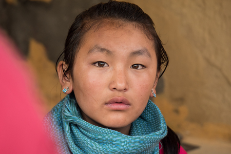 brown eyes: PUNAKHA DISTRICT BHUTAN  SEP 10 2014: An unidentified local Bhutanese girl with brown eyes looks at camera on September 10 2014 in Punakha Bhutan.
