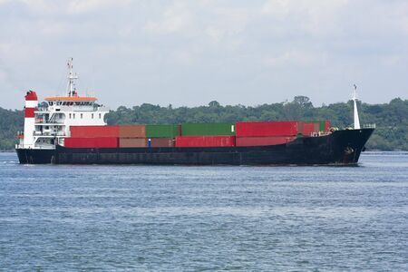 barge: Container ship leaving port in the tropics