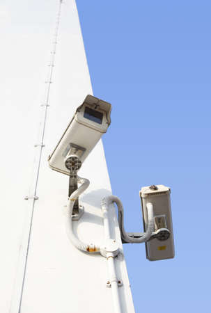 Two security cameras mounted on concrete wall photo