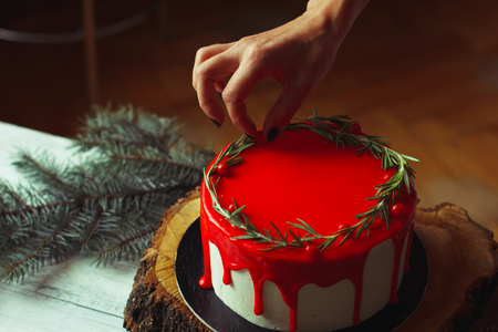 decorating: Decorating process of homemade Christmas red ganache cake by womans hands with rozmarine and red berries over old white wooden table with holly branch and chestnuts. Dark rustic style.