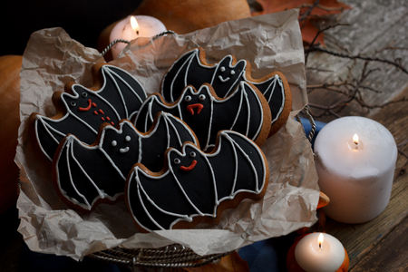 Halloween bats sugar cookies with decorations, candles light and wooden old background Stock Photo