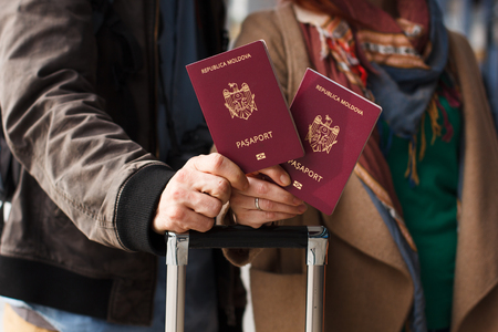 Couple Hand holding Passport . Traveler with Luggage Travel concept. People tourism. Biometric Moldavian passports
