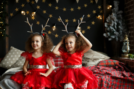 Cute curly twins girl sitting on the bed in decorated xmas room, on Christmas evening 2018 near New Year fir tree with lights and garlands. Sisters wearing red dresses and deer corns hoop