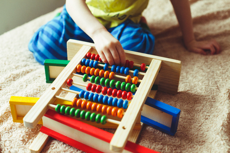 Hand of little boy playing with abacus. Clouse up picture of curly cute toddler playing with wooden toy. Stock Photo