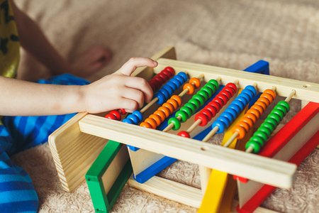 Hand of little boy playing with abacus. Clouse up picture of curly cute toddler playing with wooden toy. Reklamní fotografie