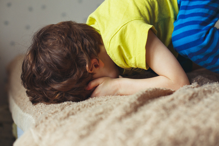 Tired toddler boy lying on the bed with his face down Stock Photo