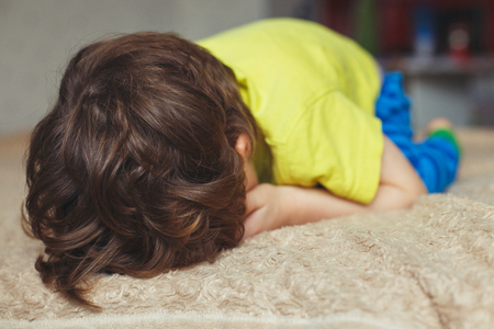 Tired toddler boy lying on the bed with his face down. Crying little kid Stock Photo
