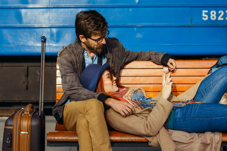 Digital technology and traveling. Young loving couple in hipster wear using tablet computer while sitting in the train station waiting for train