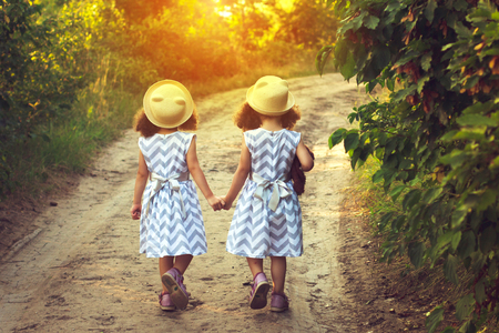 Back view of two little girls holding hand and walking together in the park in vintage color tone
