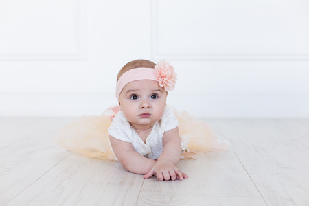 A baby girl is crawling along the floor with an inquisitive and wondering look on her face. Horizontal shot. Cute 6 months girl