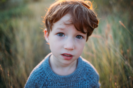 Kid portrait, sad concentrated baby. Deep blue beautiful eyes. Children, baby, people, psychology, sadness, feelings concepts. Conceived boy thinks and looks into camera. Pretty face and clever look Stock Photo