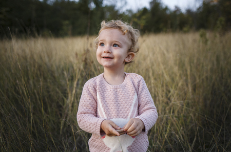 Cute curly hair blonde girl. Toddler in pink sweater. Outdoor baby portrait.
