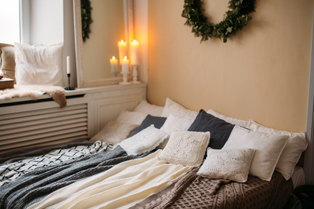 Bright cozy modern bedroom with holiday decoration. Bed with grey bedding set and knitted pillow on it, wooden rack, beautiful Stock Photo
