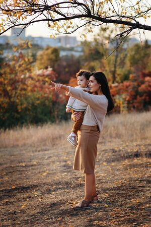 Young Caucasian mother with a boy child son baby in her hands walking and smiling in the autumn in nature Stock Photo