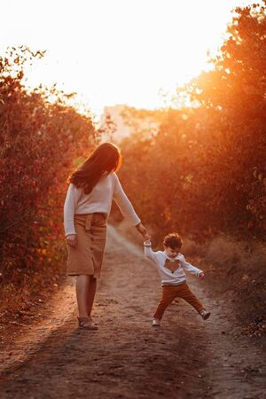 Little boy and his mother walking in the autumn park. Beauriful sunset time, red leaves
