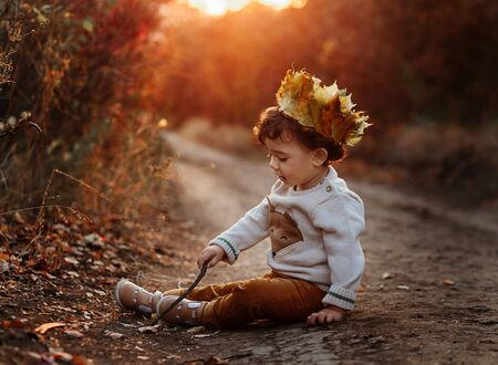 Toddler in the autumn leaves. Beautiful little child on an autumn walk looks at the falling foliage. Baby boy sitting on the autumn road. Sunset time. Crown on head