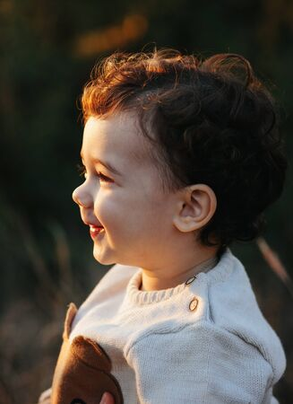 Close portrait of a sweet smiling toddler baby boy in autumn park on sunset. Curly hair boy Stock Photo
