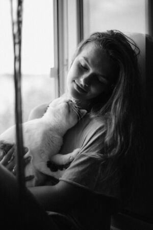 Pets Care. Young woman holding cat home. Cute cat in woman hands. Animal Love. Cat lover. Friendship. Black and white photo