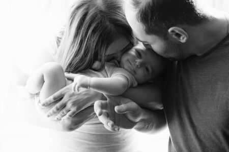 Woman and man holding a newborn. Mom, dad and baby. Close-up. Portrait of young smiling parents kissing their baby. Black and white photo