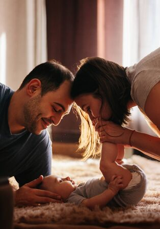 Baby with his parents playing on the bed. Happy family at home. Lifestyle cozy photos. Little boy 4 months old