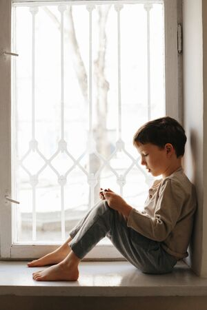 Child in home quarantine looking out of the window with his smartphone, protection against viruses during coronavirus and flu outbreak. Children and illness COVID-2019 disease concept Stok Fotoğraf - 143843633