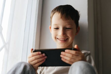 Little smiling child boy playing games or surfing internet on digital smartphone computer white isolated Stok Fotoğraf - 143874885