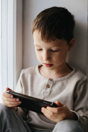 Toddler boy using tablet or smartphone. Cute five years old boy sitting at home using digital device. Stok Fotoğraf - 143874922