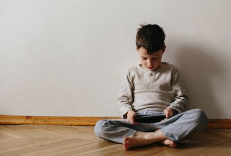 Toddler boy using tablet or smartphone. Cute five years old boy sitting at home using digital device. Stok Fotoğraf - 143874925