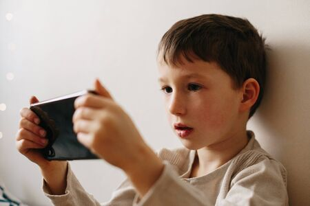 Toddler boy using tablet or smartphone. Cute five years old boy sitting at home using digital device.