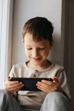 Little smiling child boy playing games or surfing internet on digital smartphone computer white isolated Stok Fotoğraf - 143874926