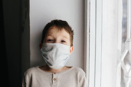5 years boy wearing surgical protection face mask sitting at home during coronavirus,covid-19 outbreak. European child concept for sickness or allergy. Quarantine time Stok Fotoğraf - 143874929