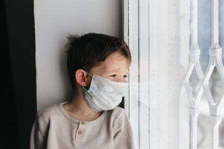 5 years boy wearing surgical protection face mask sitting at home during coronavirus, covid-19 outbreak. European child concept for sickness or allergy. Quarantine time Stok Fotoğraf - 143874949