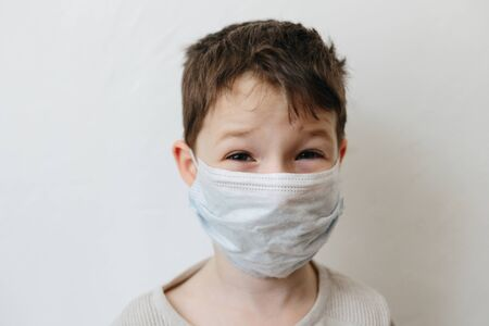 Crying toddler boy with medical mask on the face. Covid 2019 coronavirus outbreak. Sad child isolated on white. Boy at home Banque d'images