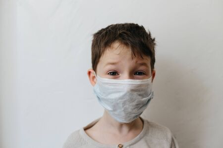 Crying toddler boy with medical mask on the face. Covid 2019 coronavirus outbreak. Sad child isolated on white. Boy at home Stok Fotoğraf - 143874959