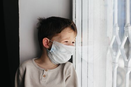 5 years boy wearing surgical protection face mask sitting at home during coronavirus,covid-19 outbreak. European child concept for sickness or allergy. Quarantine time