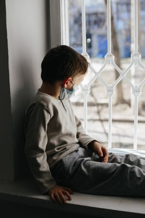 5 years boy wearing surgical protection face mask sitting at home during coronavirus,covid-19 outbreak. European child concept for sickness or allergy. Quarantine time Stok Fotoğraf - 143877113