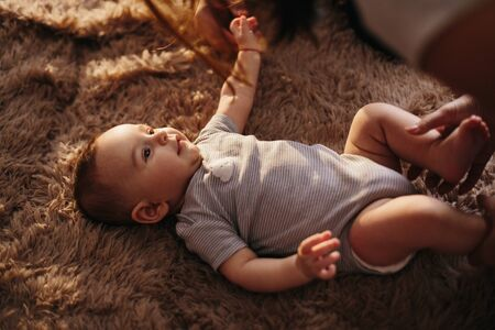 portrait of a child 4 months old lying on the bed and looking. Charming child with dark eyes lying on back,