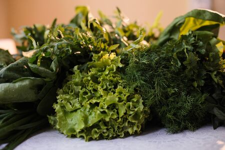 Spring vitamin set of various green leafy vegetables on the table.
