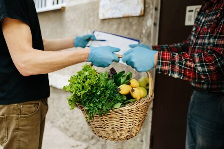 Delivery man wearing mask and gloves holding box basket full of different vegetables and greens. Customer receiving order from courier at home, organic fresh food online Stok Fotoğraf - 145406756