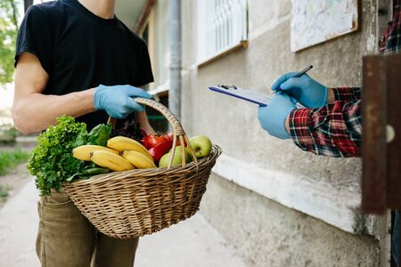 Courier giving basket with products to client near the home, closeup. Food delivery online service. Delivery service under quarantine, disease outbreak