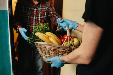 Online shopping concept. Male courier in black uniform, protective mask and gloves with a grocery basket with fresh fruits and vegetables Stok Fotoğraf - 145406759