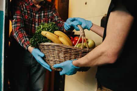Online shopping concept. Male courier in black uniform, protective mask and gloves with a grocery basket with fresh fruits and vegetables Stok Fotoğraf - 145406760