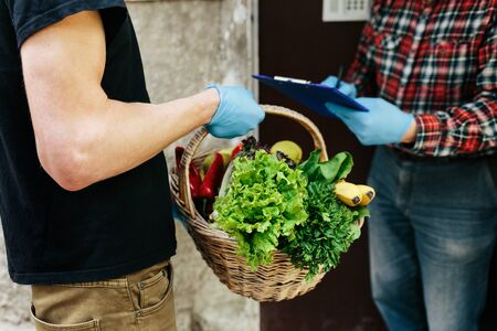 Courier giving basket with products to client near the home, closeup. Food delivery online service. Delivery service under quarantine, disease outbreak Stok Fotoğraf - 145406761